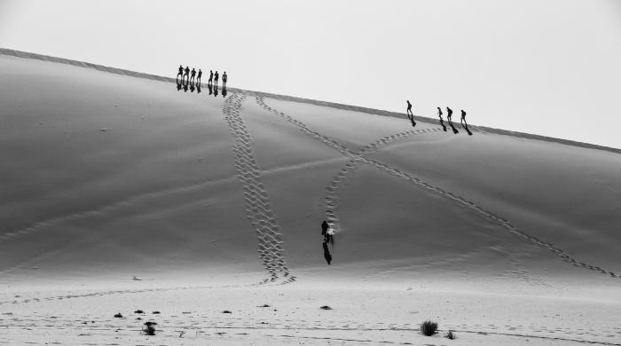 paysage noir et blanc désertique silhouettes d'hommes marchant sur une dune de sable laissant des traces derrière eux