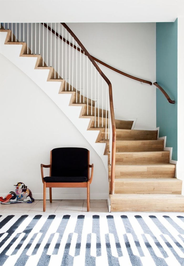 intérieur scandinave moderne avec un escalier bois et blanc au design sublimé par un pan de mur bleu canard et une jolie rampe en bois naturel