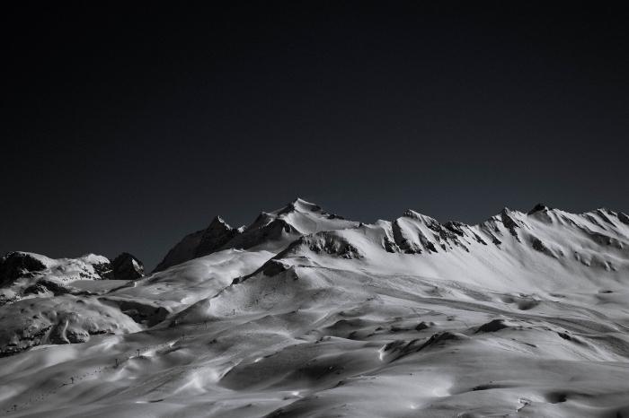 la blancheur d'une crête de montagne rocheuse couverte de neige qui se détache sur le fond du ciel noir, les plus belles images de paysages de montagne noir et blanc