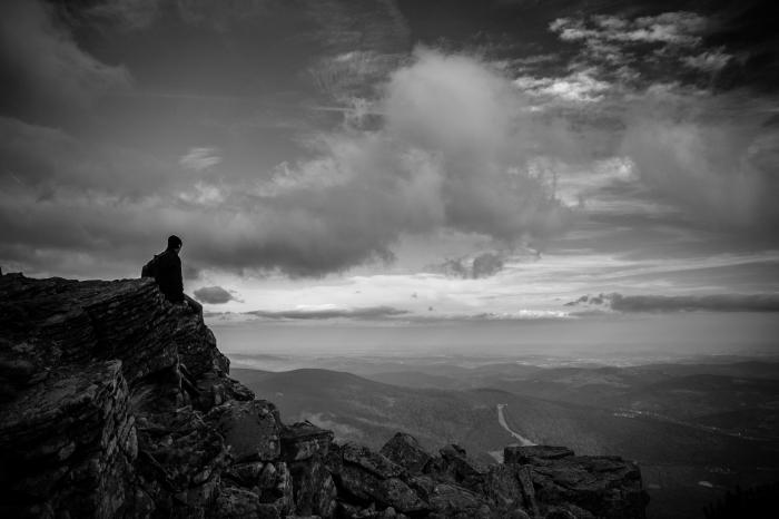 belle photo d'homme assis sur un rocher contemplant la nature sous le spectacle des nuages, portrait noir et blanc l'homme et la montagne