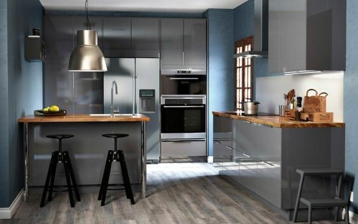 cuisine gris et bois, tabourets noirs, grande lampe style usine, armoires grises, fours encastrables