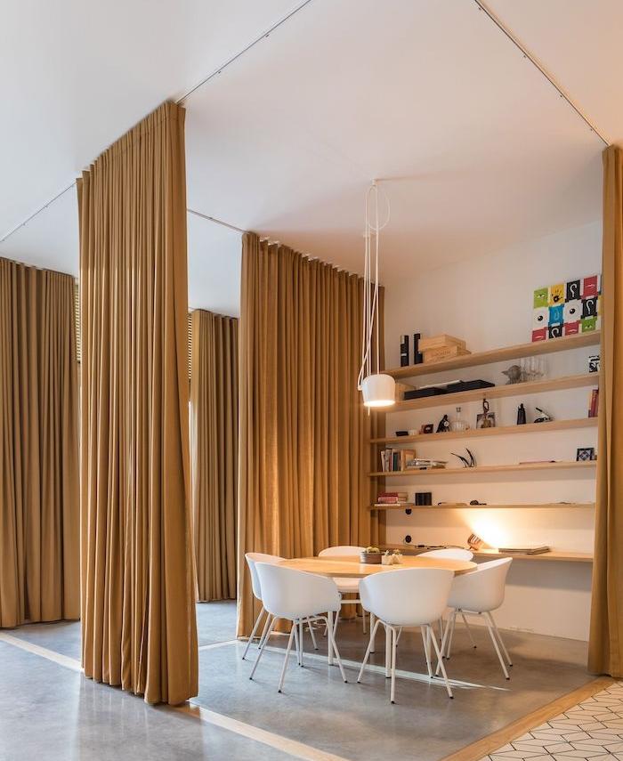 rideau séparateur sur rail couleur jaune moutarde pour isoler une salle à manger scandinave avec chaises blanches, étagère murale bois