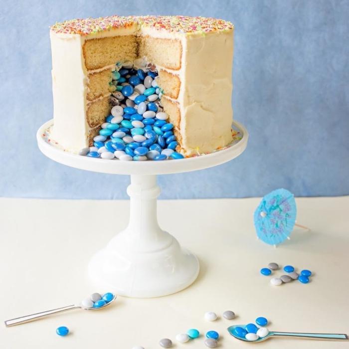 gateau pinata à la vanille pour rempli de bonbons bleus pour annoncer le sexe du futur bébé, gâteau à couches au glaçage au beurre posé sur un présentoir à gâteau