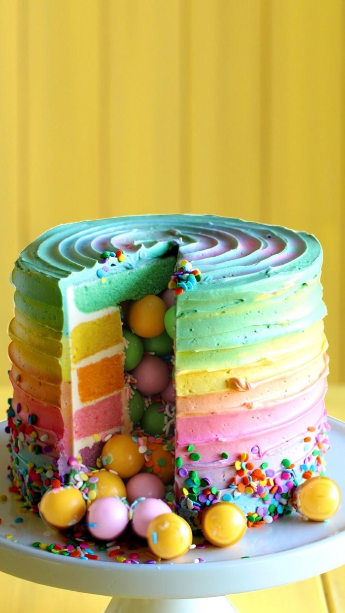 gateau arc en ciel haut en couleur rempli de bonbons, au glaçage coloré qui reprend les couleurs de l'intérieur