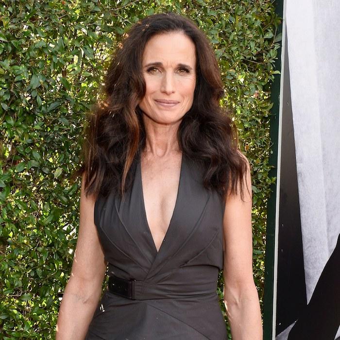modele coupe de cheveux femme 50 ans, cheveux longs ondulés avec une raie sur le coté, robe grise avec décolleté