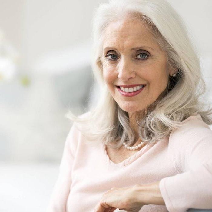 modele de coupe de cheveux longs ondulés couleur blanche, maquillage femme âgée, chemise rose, collier de perles