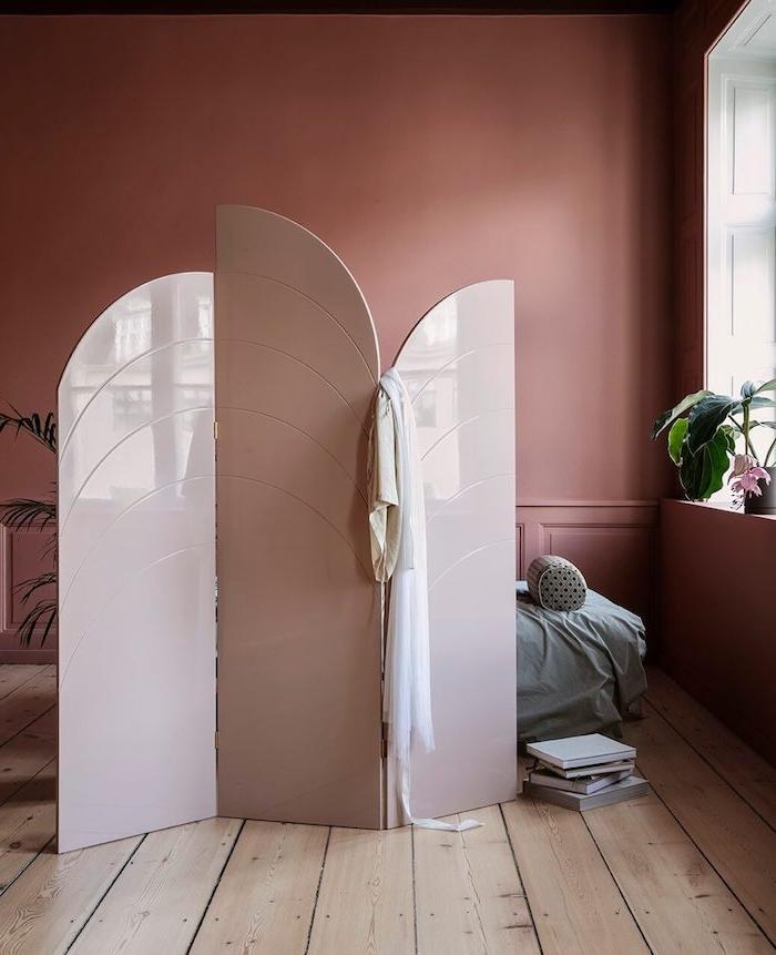 amenagement chambre femme avec murs couleur rouge cuivre et paravent rose pour cacher un coin couchage avec lit gris