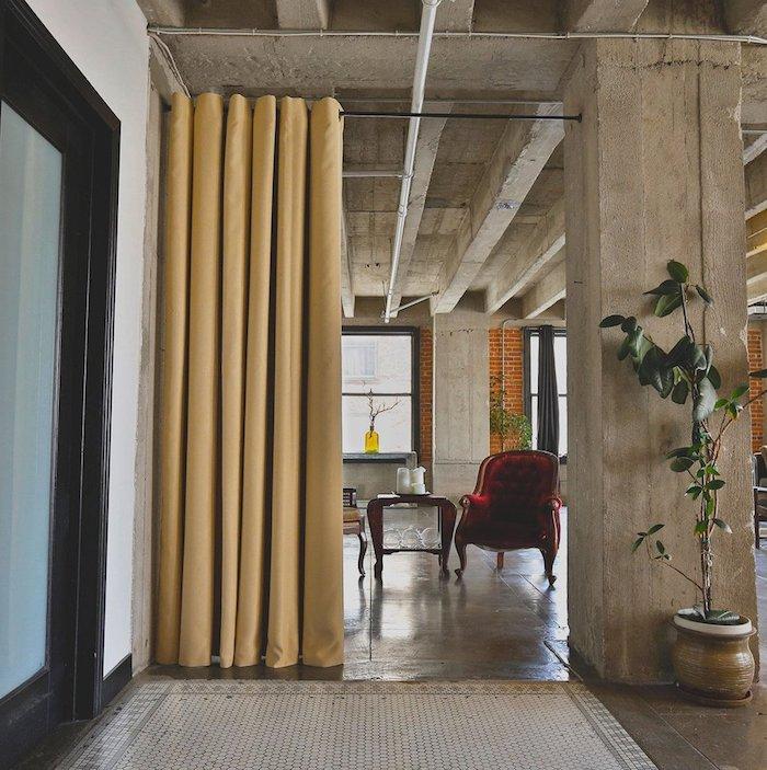 rideau jaune sur rail noir comme cloison atelier amovible, murs, plafond et colonnes de béton, fauteuil rouge bordeaux, table bois
