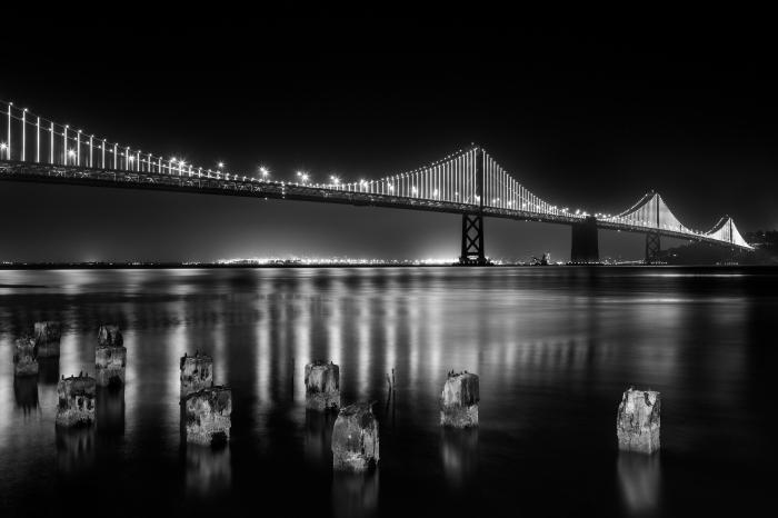 vue panoramique sur le pont de san francisco et ses mille feux reflétés dans le miroir de l'eau, un paysage urbain à faire imprimer en affiche noir et blanc