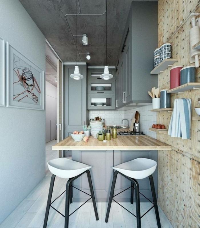 cuisine artistique, ilot en bois et gris, tabourets de bar en blanc et noir, plafond en béton, petites étagères murales