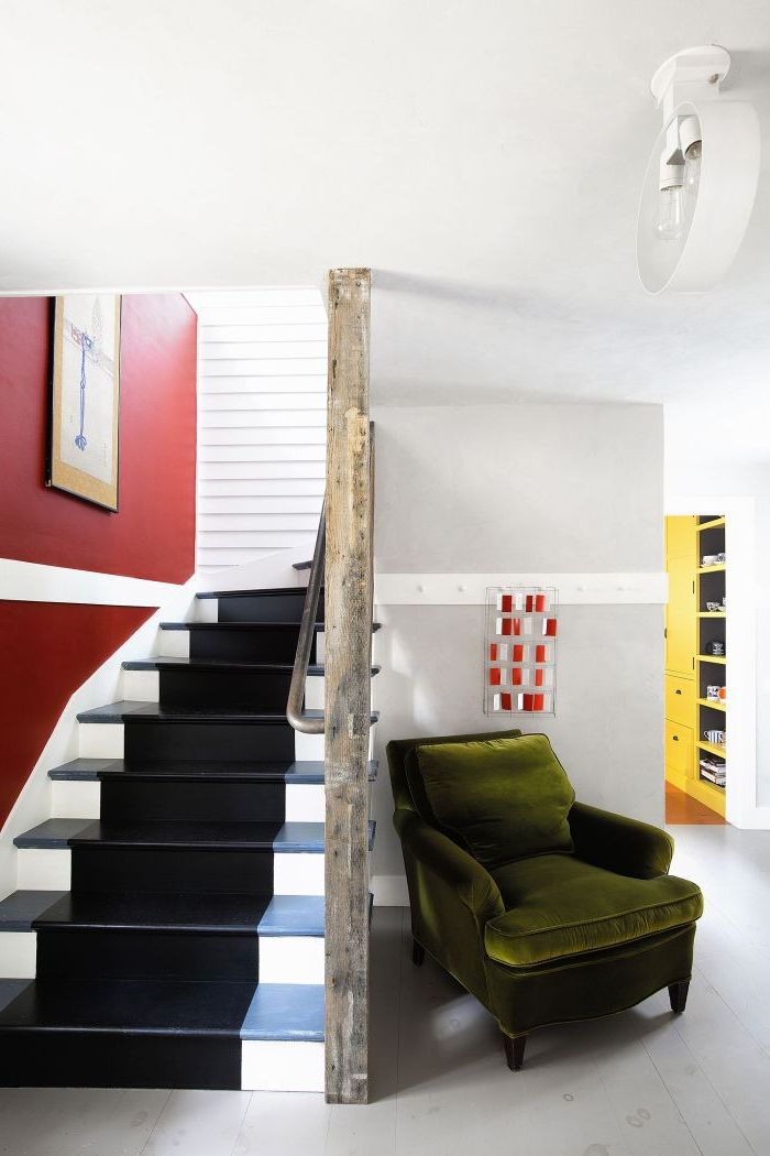 relooker un escalier un bois à l'aide de la peinture, une large bande de peinture noire qui parcourt l'escalier pour un effet tapis d'escalier, en contraste avec le blanc et le rouge qui domine la cage d'escalier