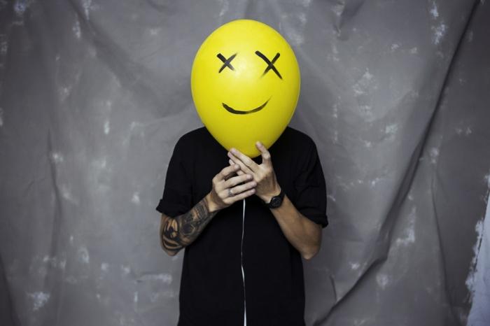 Le plus beau dessin stylisé crane, tete de mort manchette tatouage abstrait, graphique tatouage sur la main, homme qui tiens un ballon jaune