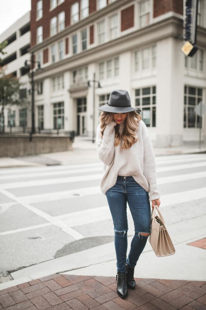 pull blanc femme, sac crème, jeans déchirés, chapeau périphérie, cheveux bouclés longs, place blanche
