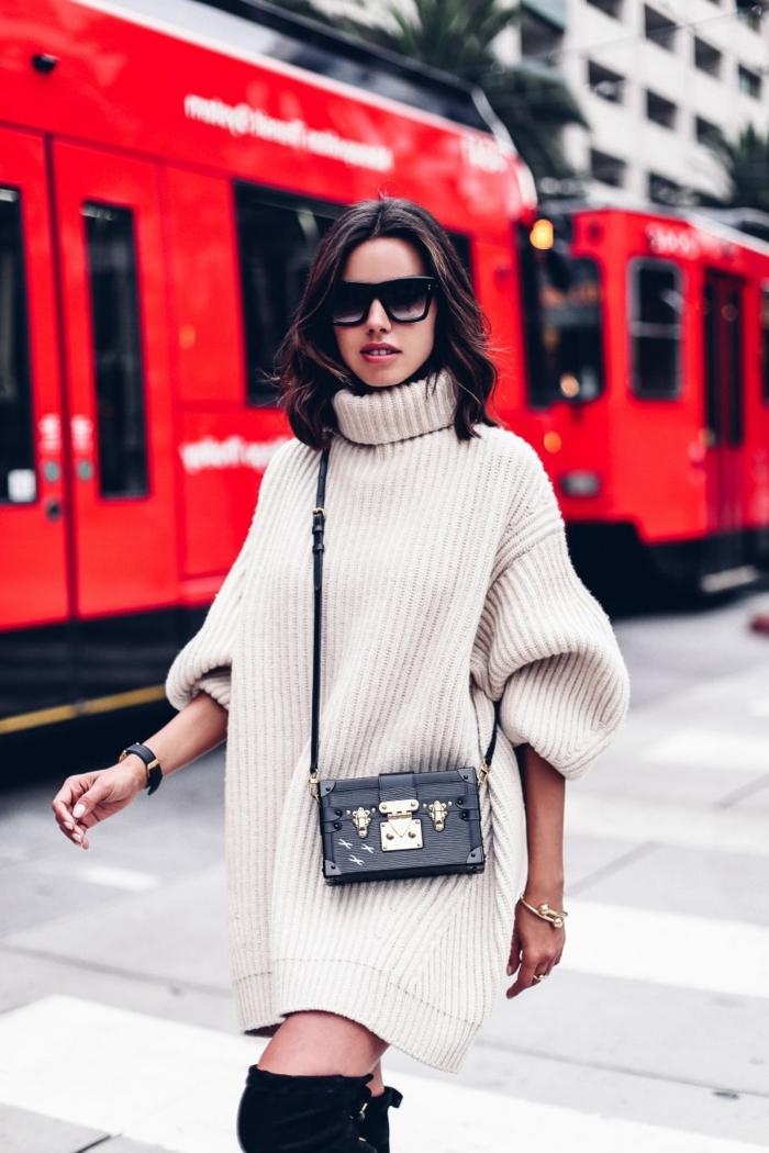 femme moderne qui porte un pull crème, petit sac noir, lunettes de soleil, cuissardes noires, pull grosse maille femme