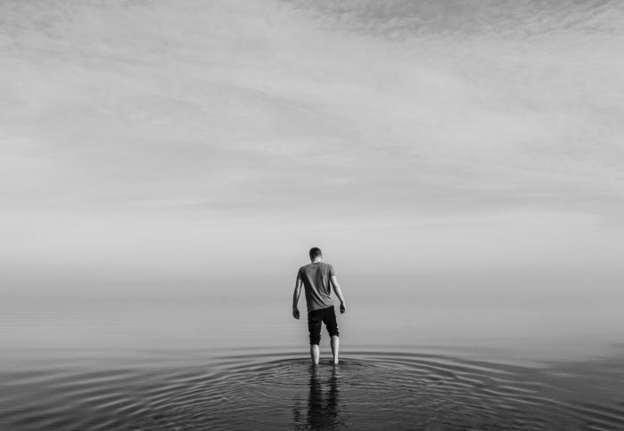 portrait noir et blanc d'un jeune homme pieds nus dans l'eau calme de la mer, en arrière plan l'horizon caché dans le brouillard