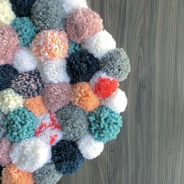 faire un pompon en laine, tapis épais et moelleux en pompons de diverses couleurs