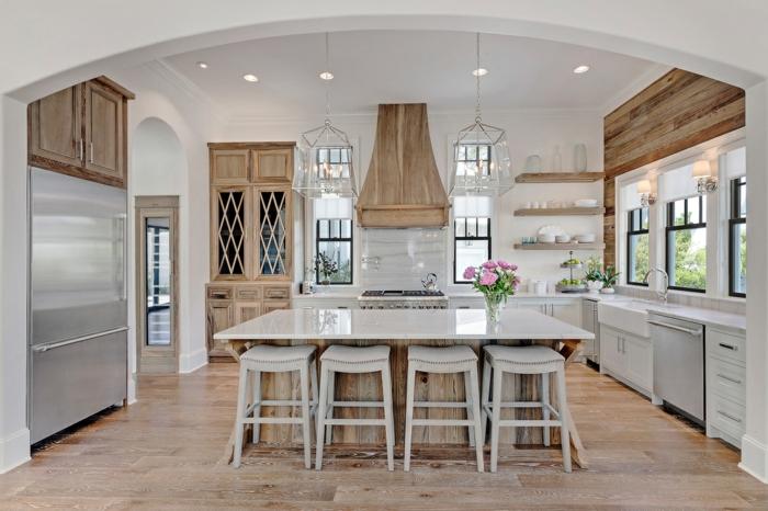 cuisine blanche et bois avec îlot central, tabourets blancs, grande armoire réfrigérée, crédence blanche, placards blancs