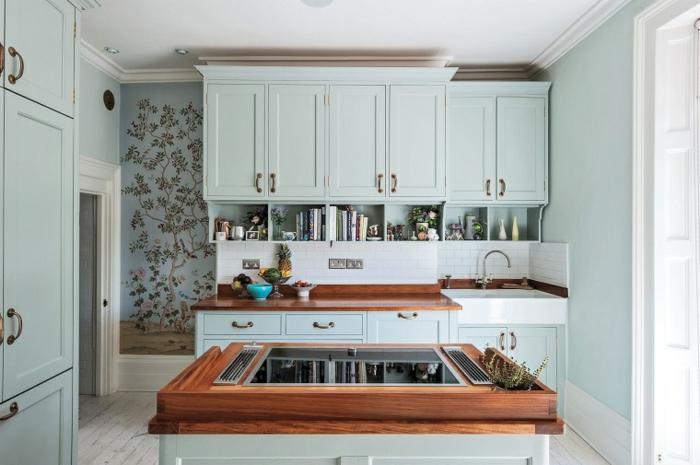 petite cuisine avec îlot central, armoires bleu pâle, sol en planches, papier peint floral