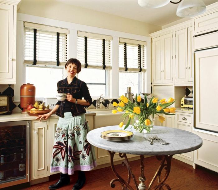 table ronde marbre, pieds en fer forgé, placards en couleur crème, rideaux blancs, petit frigo vitré, sol en bois foncé