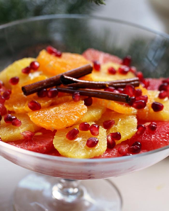 salade d'agrumes, orange et pamplemousse, bâtons de cannelle, graines de grenade, fruits pelés et arrangés dans un bol de salade
