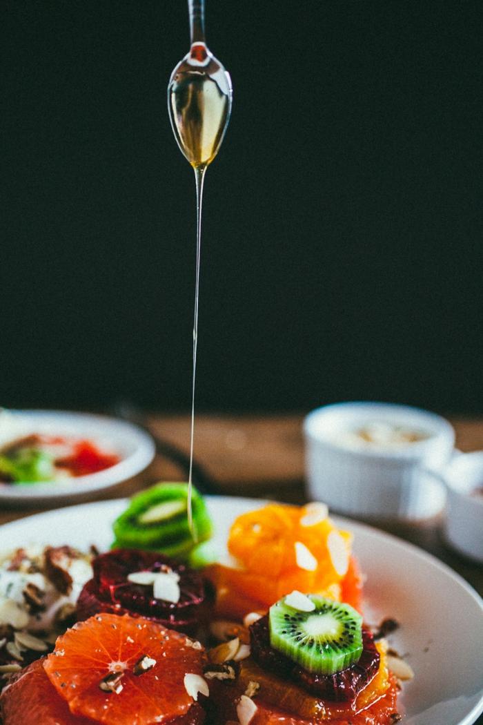 salade fruits multicolore, garni de miel, agrumes, noix effilés, kiwi, orange, pamplemousse, dessert de fete aux fruits