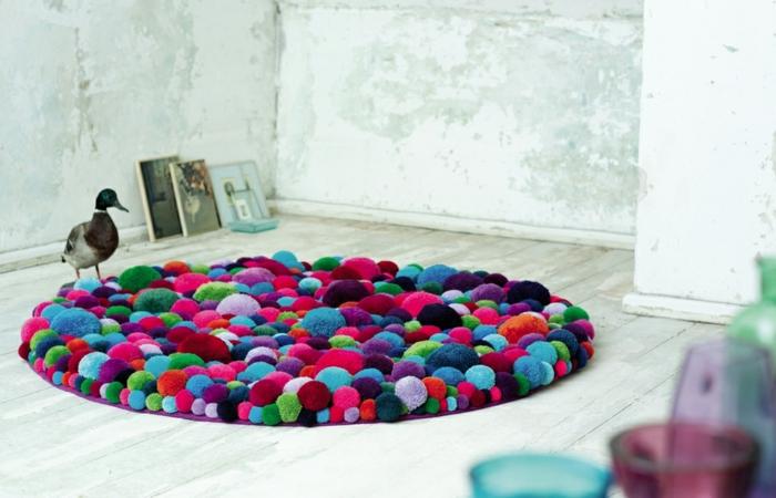 pompons en laine assemblés en tapis rond multicolore, sol en lattes blanches, murs en béton, bouteilles et tasses acryliques
