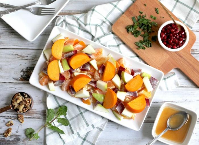 plat d'hiver servi sur une assiette blanche rectangulaire, planches de bois, sirop pour salade de fruits, noix de noyer