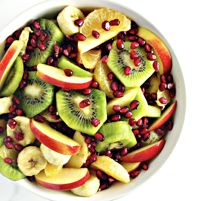 bol blanc rempli de fruits saisonniers, pommes en tranches, orange, kiwi, bananes, parsemés de graines de grenade