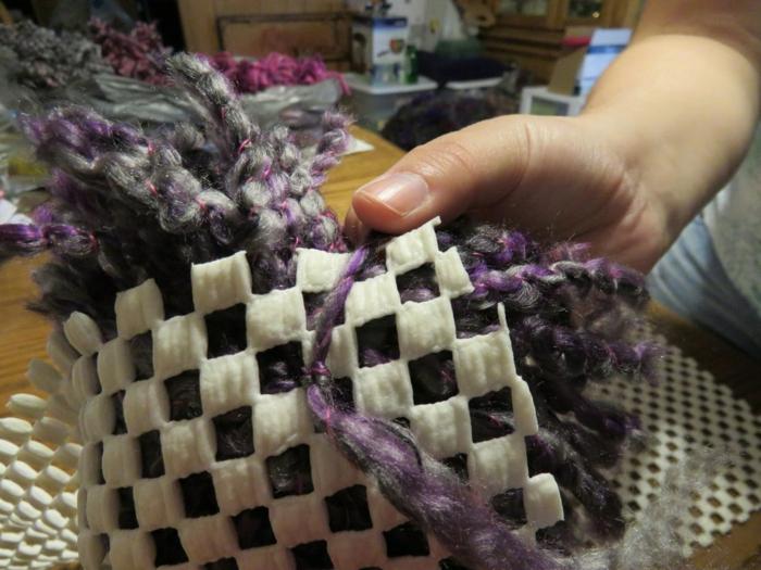 le dos d'une toile canevas, noeud avec les fils en laine de grands pompons pourpres, diy tapis laine
