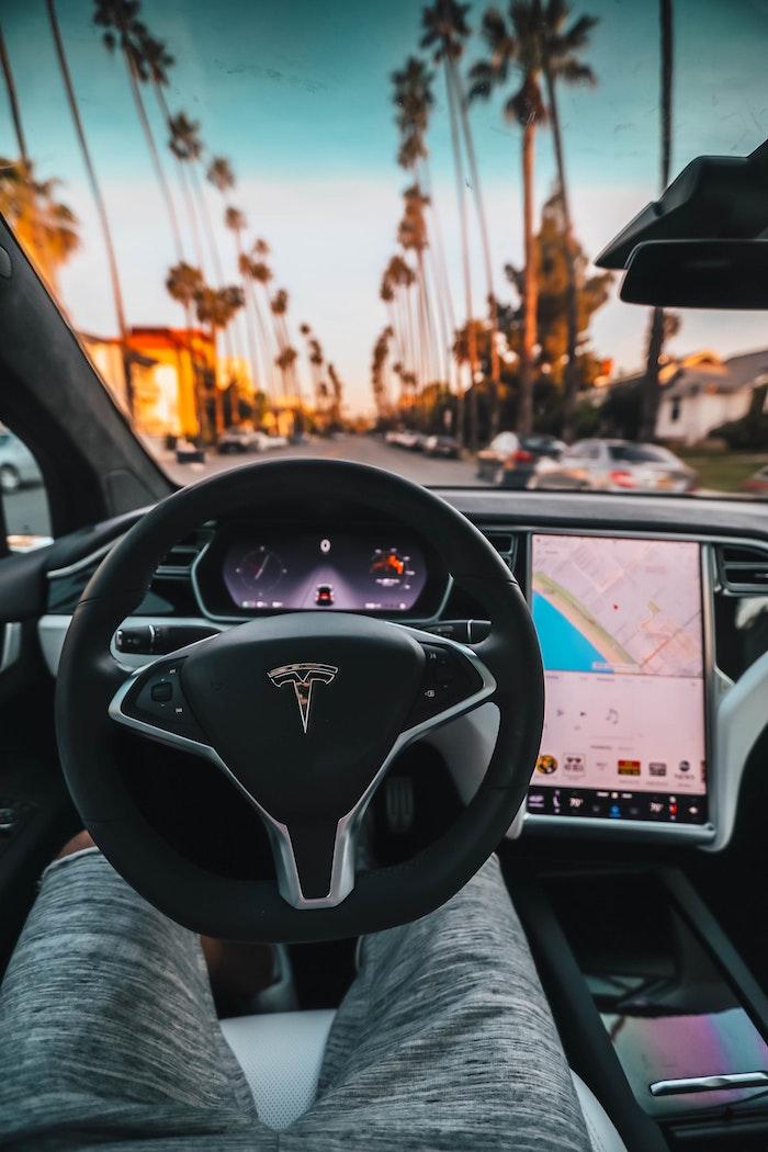 Palmes sur les rues de Los Angeles, l'intérieur d'une voiture électrique Tesla Model 3