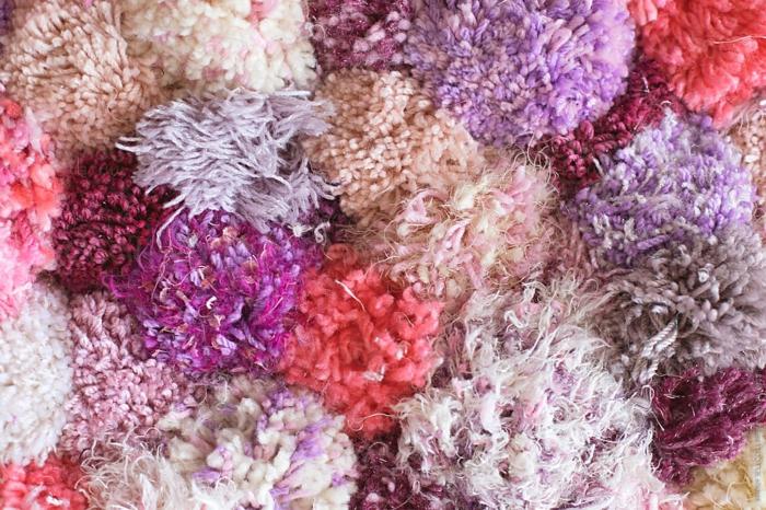 pompons colorés en couleurs lilas, roses et pourpres, diy tapis à faire avec ses propres mains
