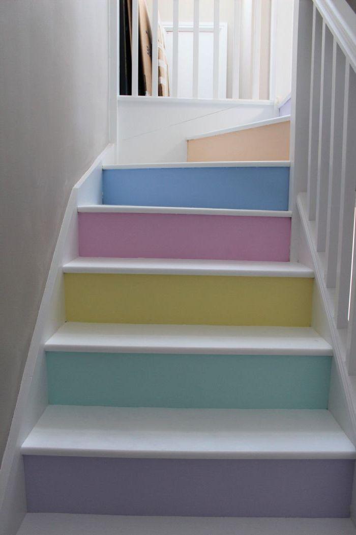un escalier peint blanc aux contremarches en différentes teintes pastel qui dynamisent l'espace tout blanc de la cage