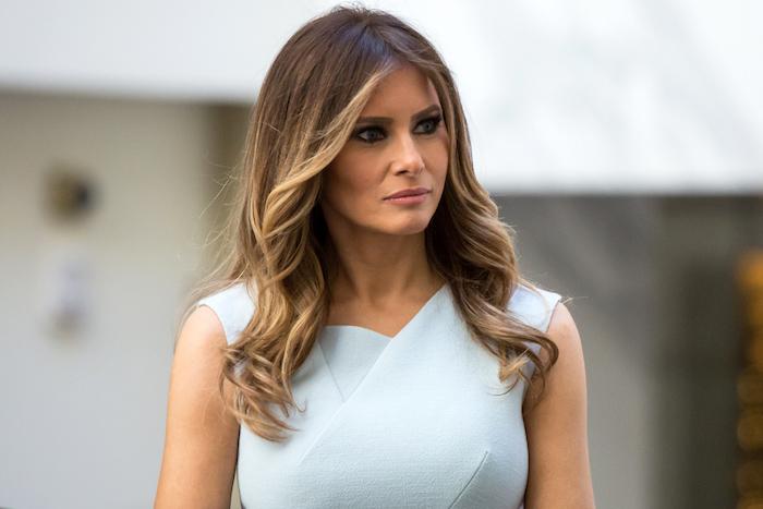 melania trump avec une coiffure longue balayage blond femme mèches encadrant le visage, robe bleu ciel