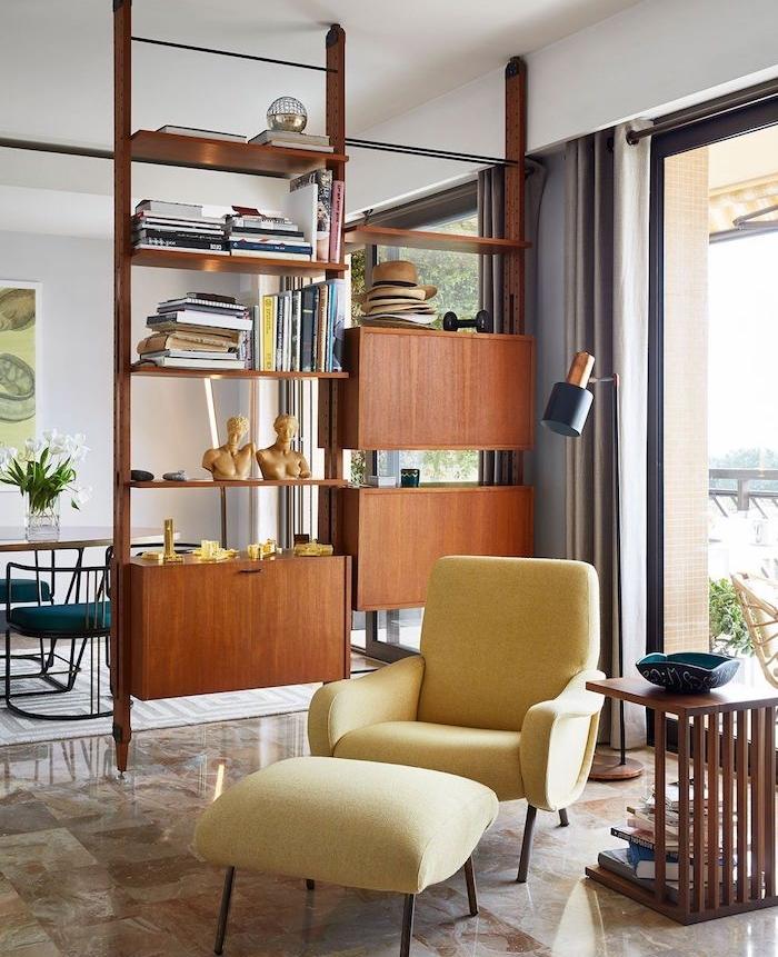 meuble de separation en bois avec des étagères et tiroirs séparer un salon et salle a manger, fauteuil jaune, carrelage de luxe