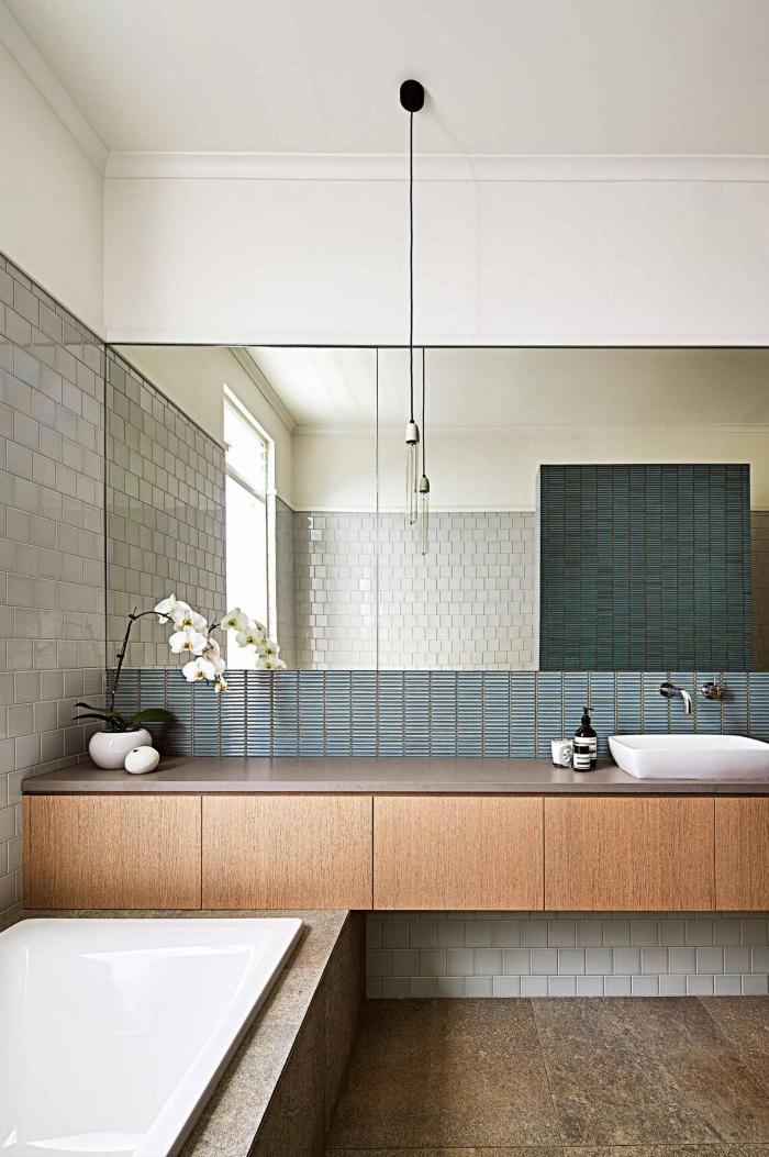 aménagement d'une salle de bains vintage équipée d'un grand meuble-lavabo suspendu à finition bois, crédence en mosaïque en tons du vert