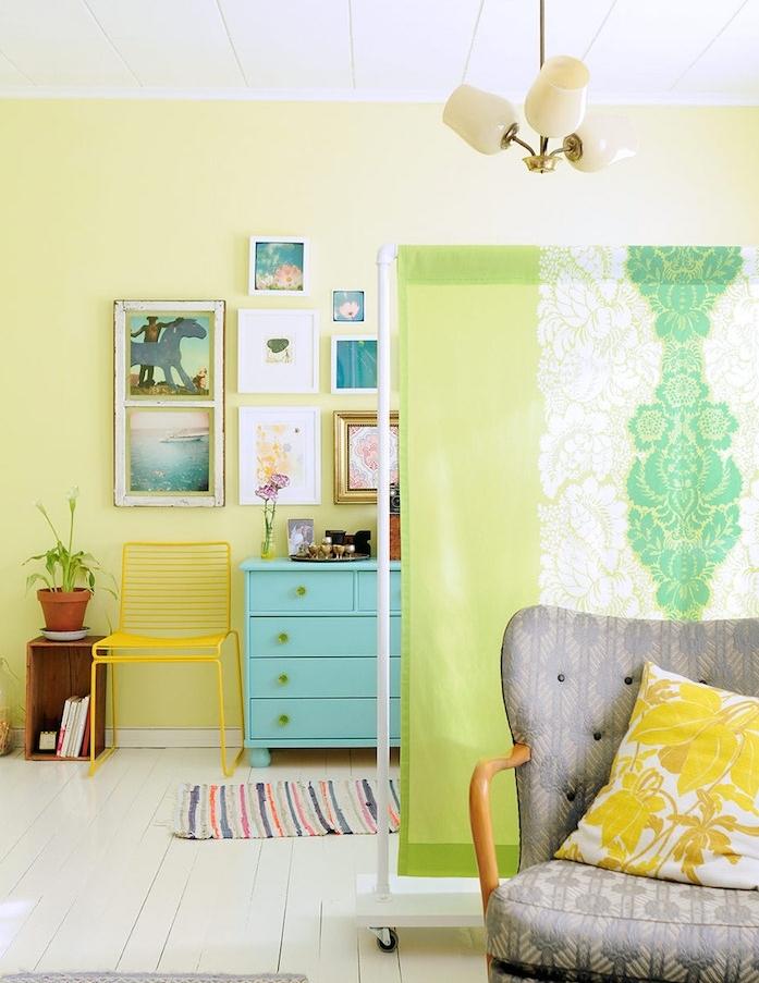 toile de séparation à motif orientaux vert et blanc, modele de cloison amovible, deco inteireur en vert, commode bleu, fauteuil gris, deco murale de cadres