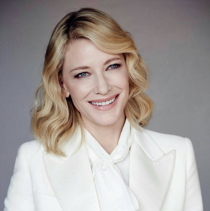 carré long plongeant ondulé sur cheveux blond avec une frange asymétrique de coté ondulé, tailleur femme blanc chic