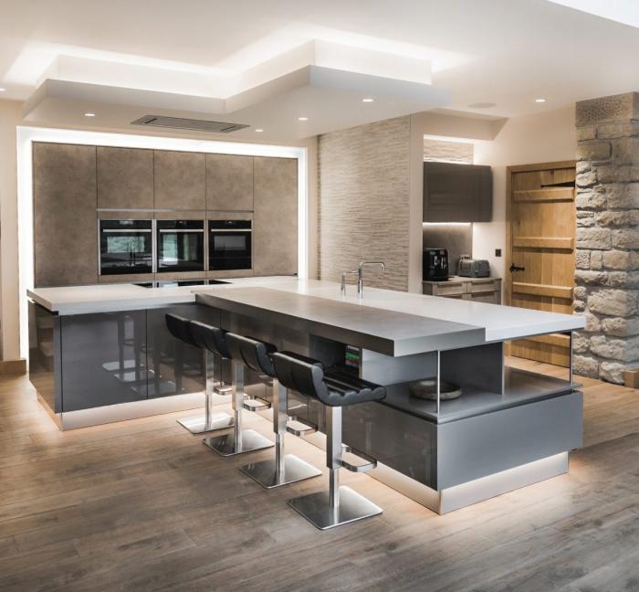 cuisine moderne en bois et blanc, parement mural en pierre, îlot en angle aux surfaces lisses