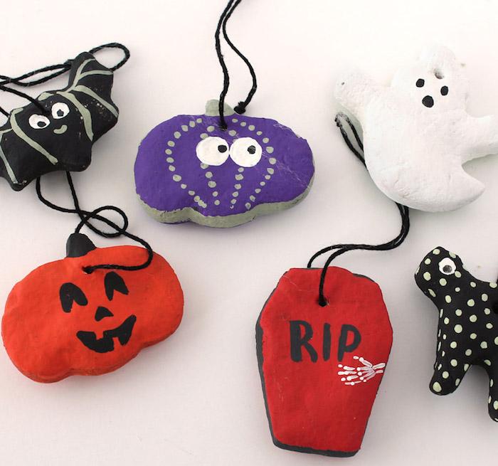 décoration halloween diy faite en pate sel avec différents symboles fantome citrouille tombe chauve souris et peinture pour activité manuelle enfants vacances