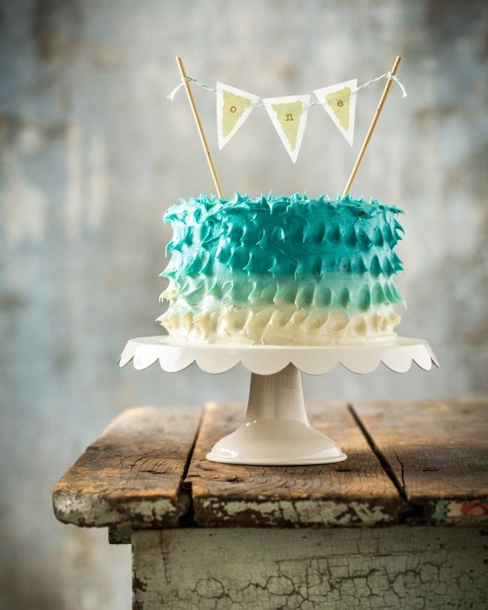 joli gateau anniversaire enfant 1 an au glaçage dégradé posé sur un présentoir à gâteau blanc et décoré avec une bannière à fanions