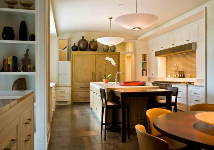 cuisine petite surface design traditionnel, îlot de cuisine blanc, table ronde en bois, chaises jaunes, armoire en bois et pots en argile