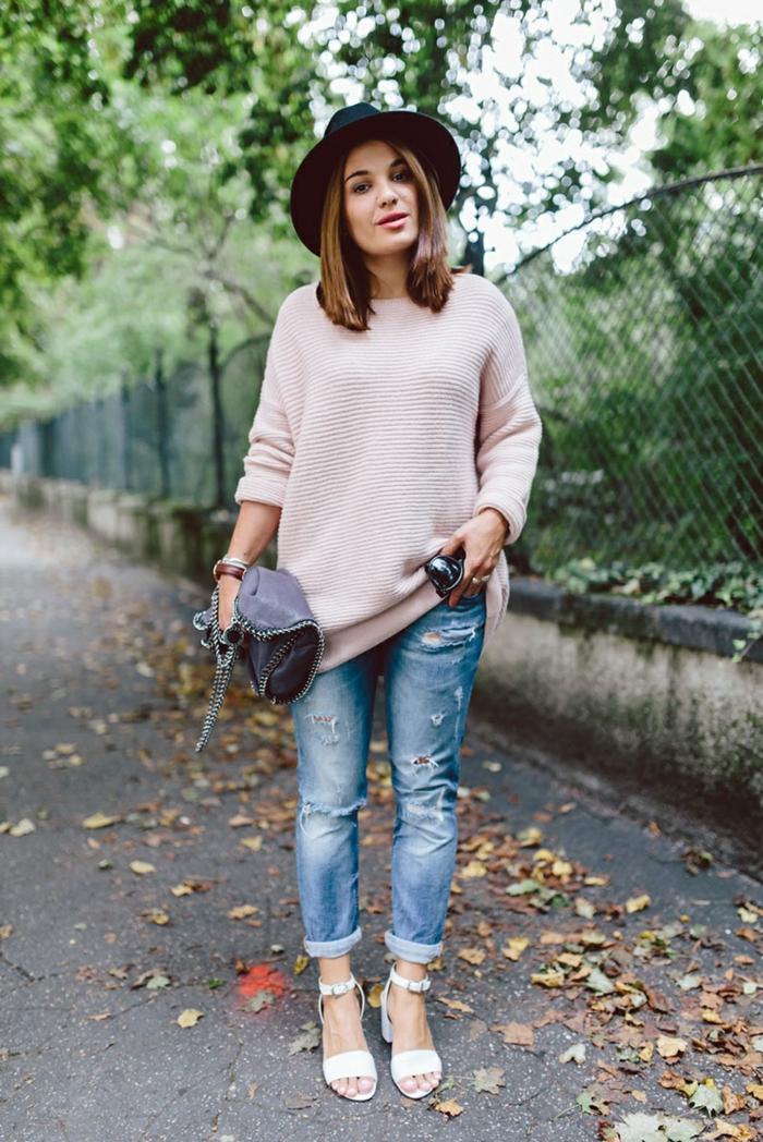 pull rose, jeans déchirés, sac gris, chapeau avec périphérie, sandales crème, feuilles tombées au sol