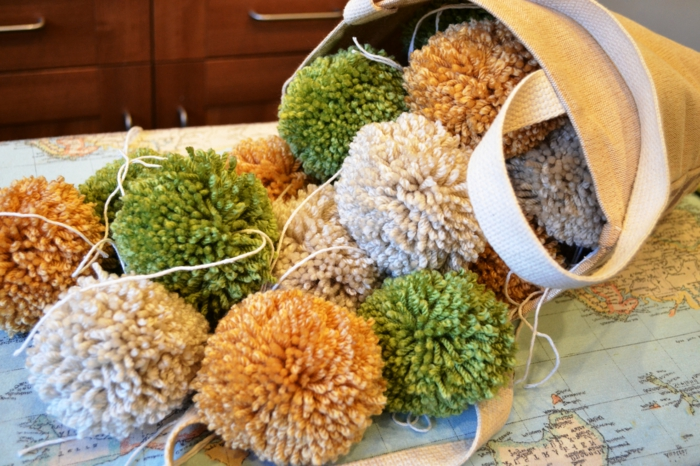 panier rempli de pompons grande taille en vert, orange et crème, faire des pompons en laine