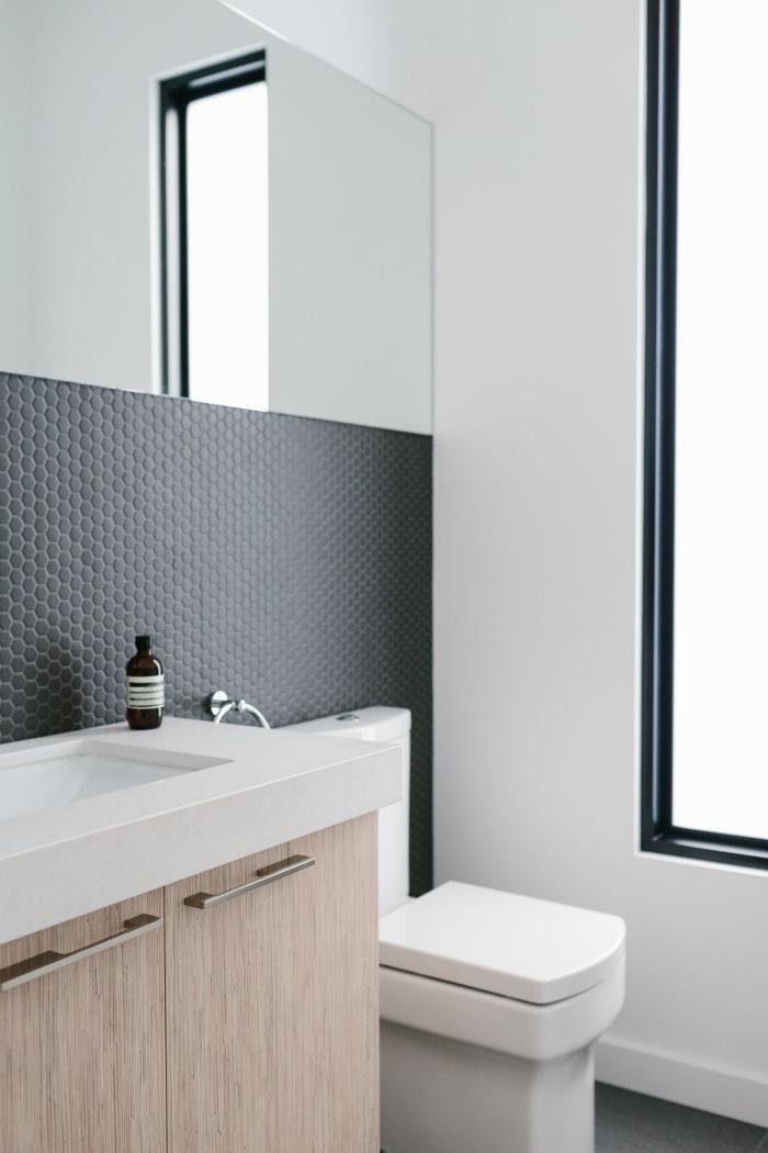 une crédence adhésive imitation mosaique hexagonal à finition noire mate qui apporte une touche d'élégance à la salle de bains blanche