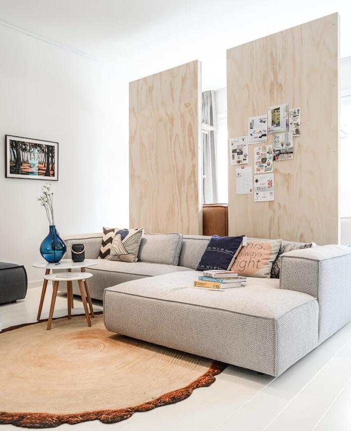 cloison coulissante avec des panneaux de bois clair, canapé d angle gris, tapis imitation tronc d arbre, tables basses scandinaves, carrelage blanc