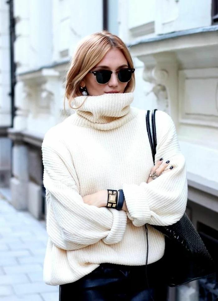 pull beige femme, deux bracelets statement, cheveux dans le col du pull, pantalon en cuir