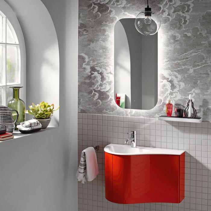 un meuble sous vasque suspendu à finition rouge en contraste avec le revêtement en papier peint et carrelage mural de mosaïque blanc et e