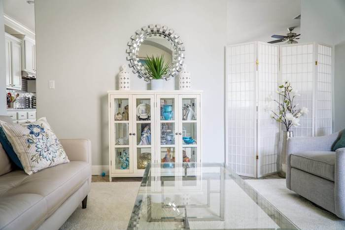 paravent blanc pour créer un coin d intimité dans un salon gris et blanc, avec fauteuil et canapé gris, table verre et vaisselier blanc