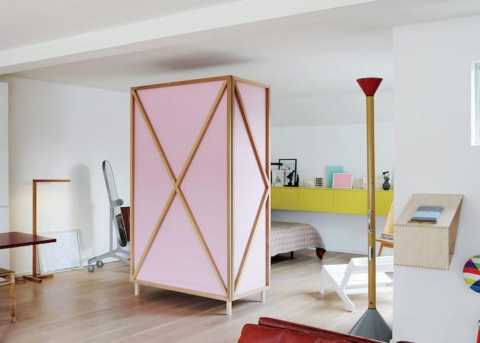 paravent de separation couleur rose et bois pour décorer une chambre à coucher design avec lit, rangement mural couleur jaune, parquet clair