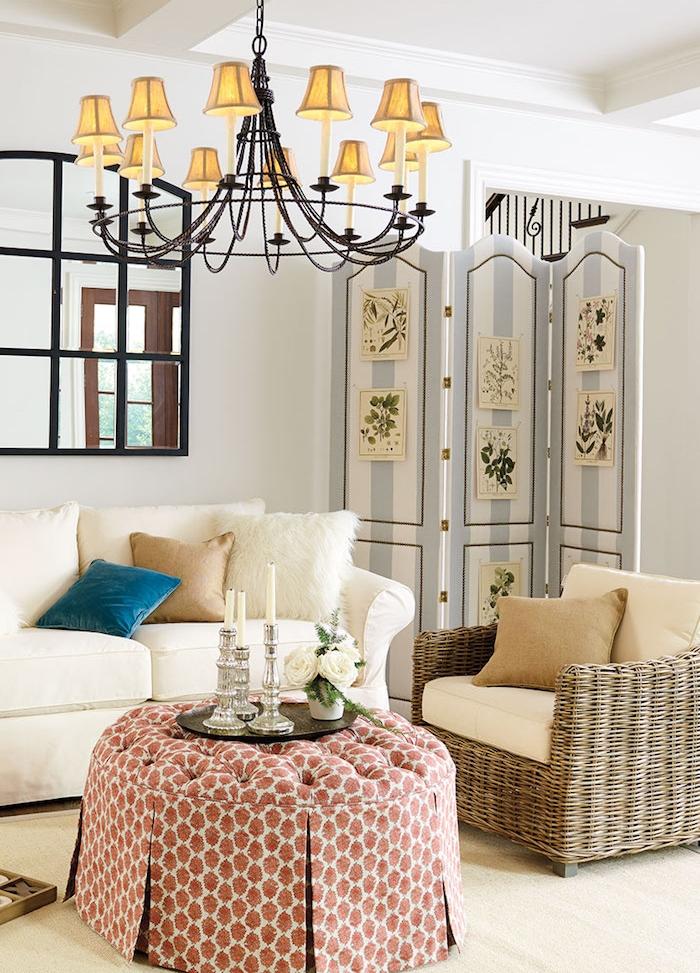 paravent vintage dans un salon décoré à canapé blanc cassé, fauteuil tressé, table basse ronde, parquet bois clair, lustre original vintage